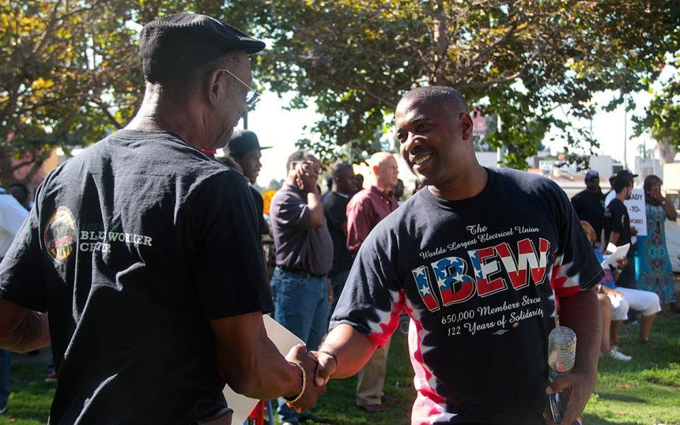 Shomari Davis, of the IBEW union's Local 11, shakes hands with Lloyd Cooks, a painter and fellow member of the Black Labor Construction Council. E. Tammy Kim for Al Jazeera America