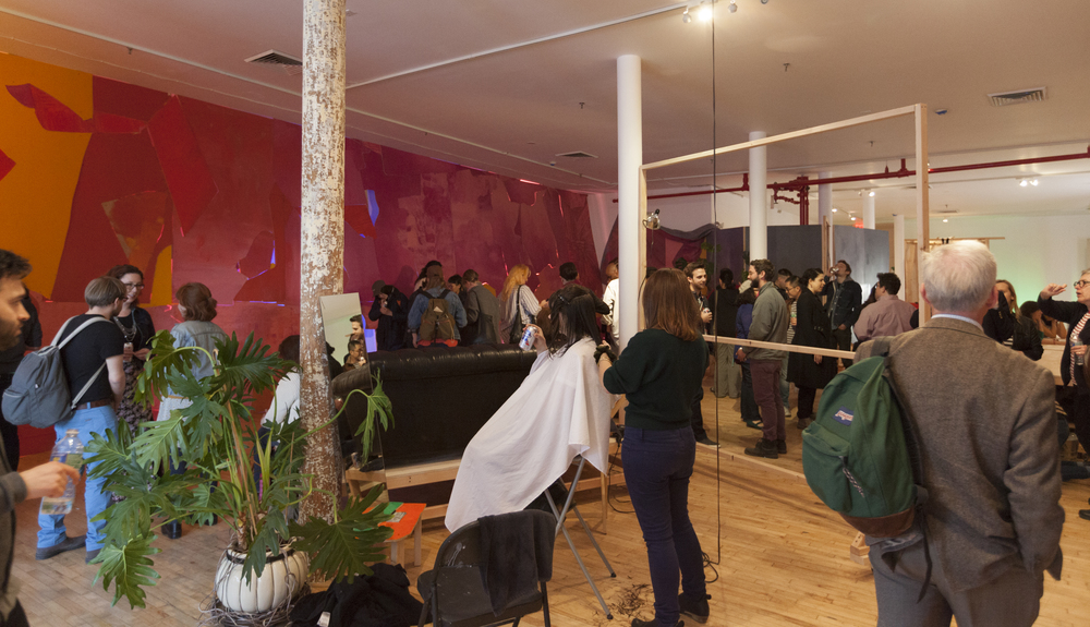 Foreground: Artist Brittany Mroczek cuts a clients hair at the opening of group show   you know it when you feel it   as part of Lisi Raskin's   Recuperative Tactics  . Background:   Flat Screen (Pink Wall)   by Lisi Raskin, Art in General, April 19, 2014. Image credit: Steven Probert