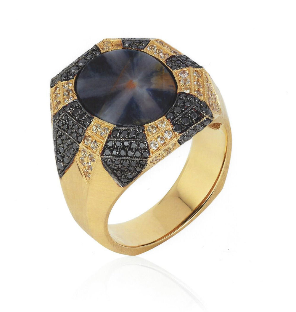 "2017 Spectrum - 1st Place Men's Wear    Ricardo Basta Fine Jewelry & E. Eichberg Jewelers    18lk yellow gold with black rhodium ""Estrella"" ring featuring a 7.50 ct starburst trapiche Sapphire accented with black Diamonds (.64 ctw) and yellow Sapphire melee (.52 ctw)."