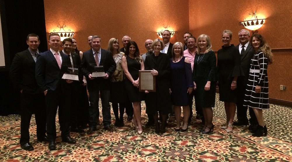 Left to right: Mitch Ohmann, Tyler Cotner, Angelo Bradford (holding award), Hilary Peters, Weston DeHart, Jeff McClure (holding award), Summer McClure, Cary DeHart, Brandi Whitehead, Frank LeForce, Jan Dunkin, John Hobson, Johnna Moses, Terry Wisely, Jesse Guerrero, Mary Roberts, Cris Callins, Kent Dalrymple and Antonina Criddle