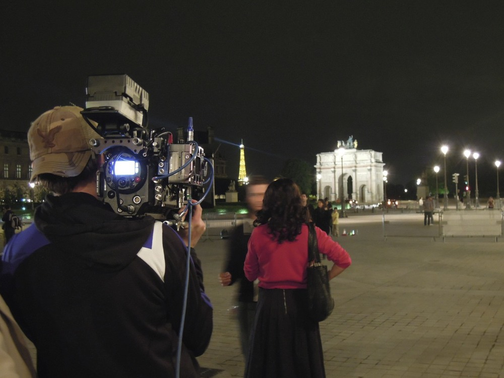 Brandon Cox, Director of Photography, and Julia at the Louvre. The Arc de Triumphe is lit up in the distance.