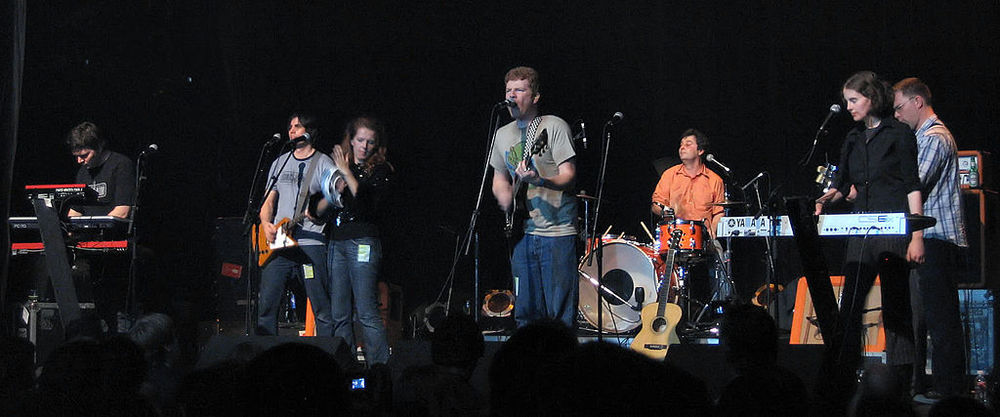 Left to right:  Blaine Thurier ,  Todd Fancey ,  Neko Case ,  Carl Newman ,  Kurt Dahle ,  Kathryn Calder ,  John Collins.  Image credit: Simon Law , via Wikimedia Commons.