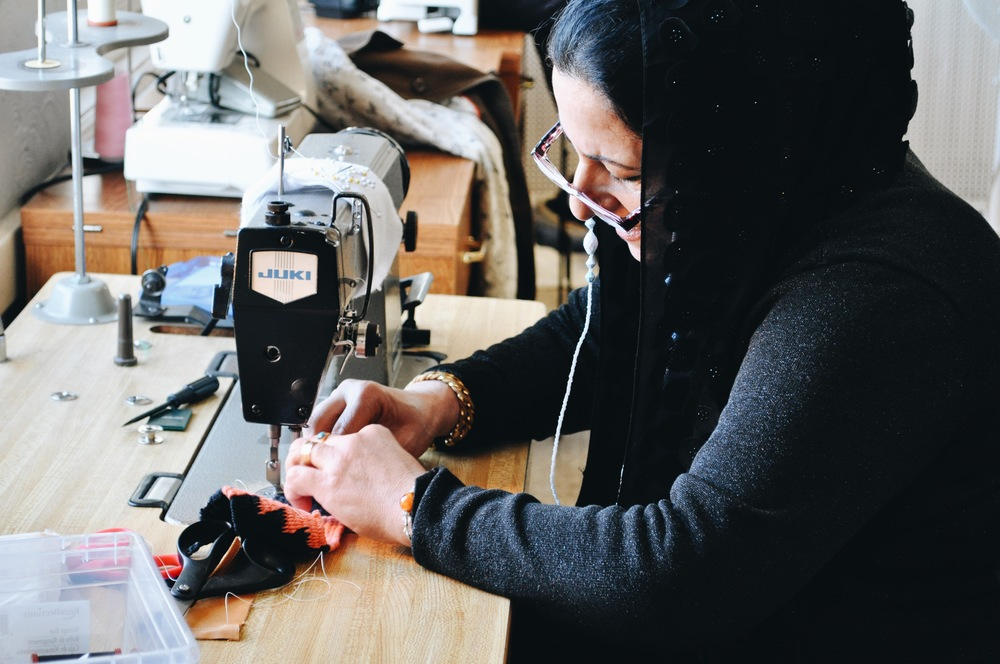 Artisan Saleemah attaching leather to the woven piece of the belt