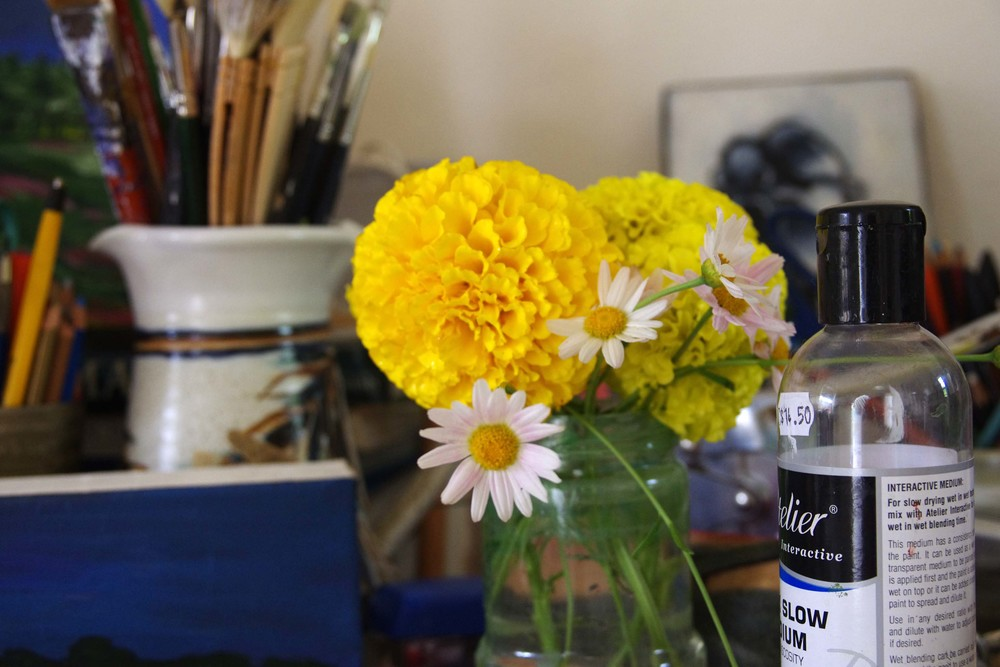 Studio flowers...in the brush washing jar. And the bottle of acrylic medium my son emptied out.