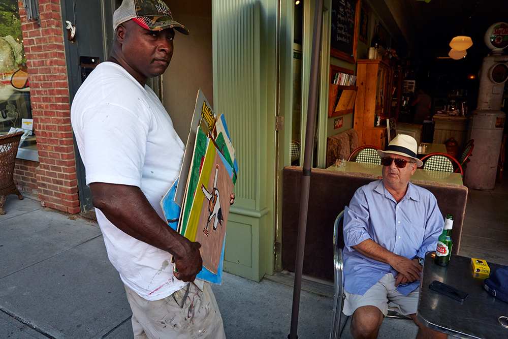 Earl Swanigan offering his paintings to a customer at Le Gamin, Hudson, NY