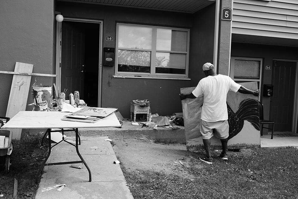 Earl Swanigan working in his outdoor studio in front of his apartment