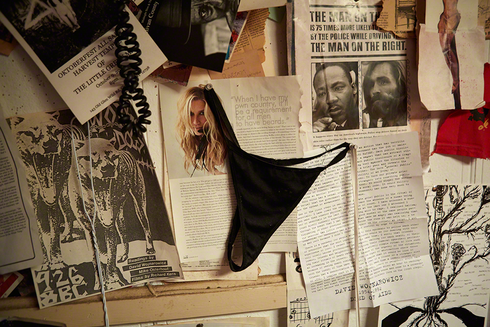 Kitchen wall with newspaper clippings, a random g-string and other stuff.