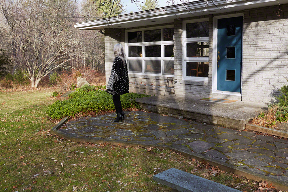 Elllison-Prat in front of her 1954 Mid-century house on 1.5 acres she purchased with her hubby Alex in 2014. Studded coat by Funkanova Vintage and Rochas lace-up boots.