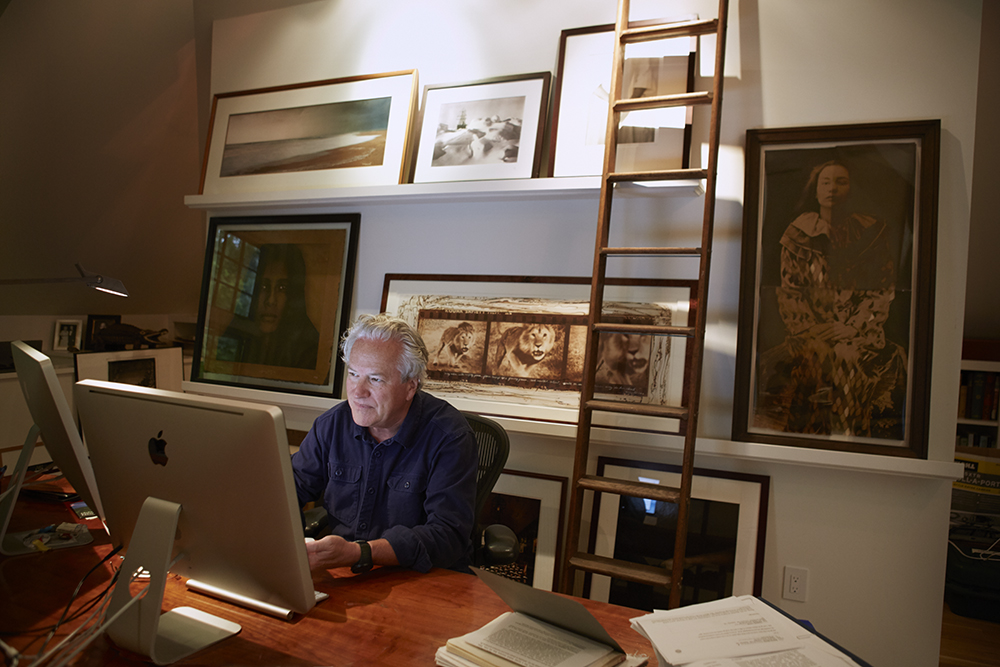 In his home office. On the wall: Shackleton's 'Endurance' by Frank Hurley, Peter Beard's  Loliondo Lion Charge , 1964 and  The Clown  by Luis Gonzalez-Palma among others.