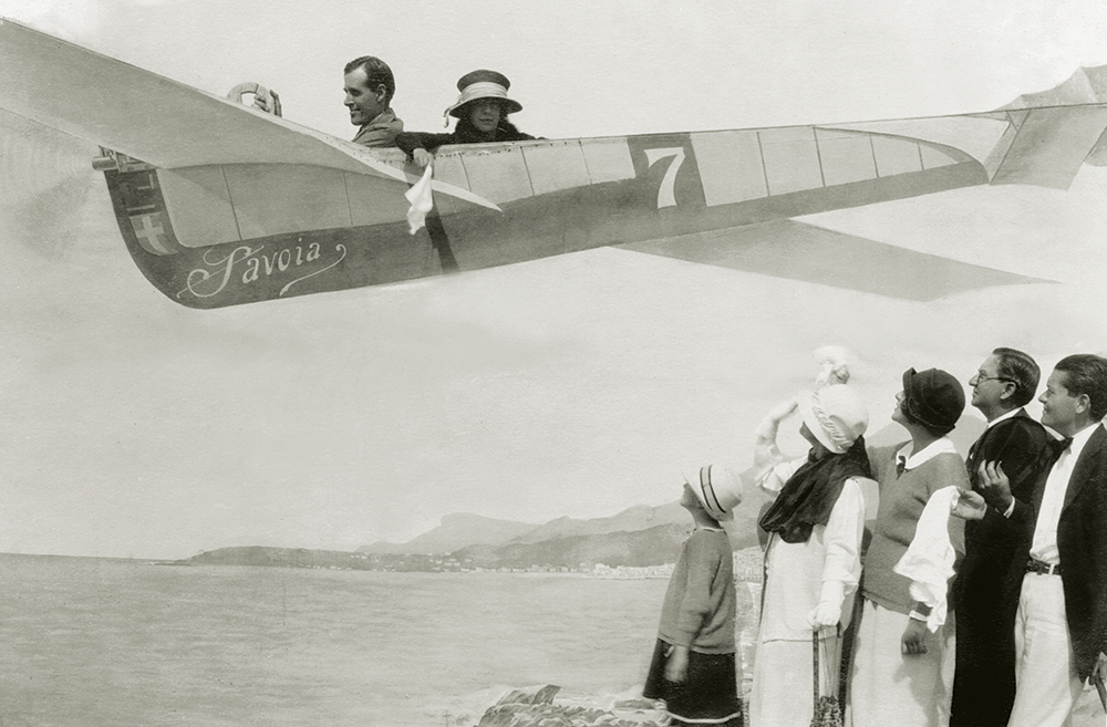 Helen waving goodbye to the Dows family as she pretends to be a passenger in a painted backdrop of a Savoia plane in Corsica.