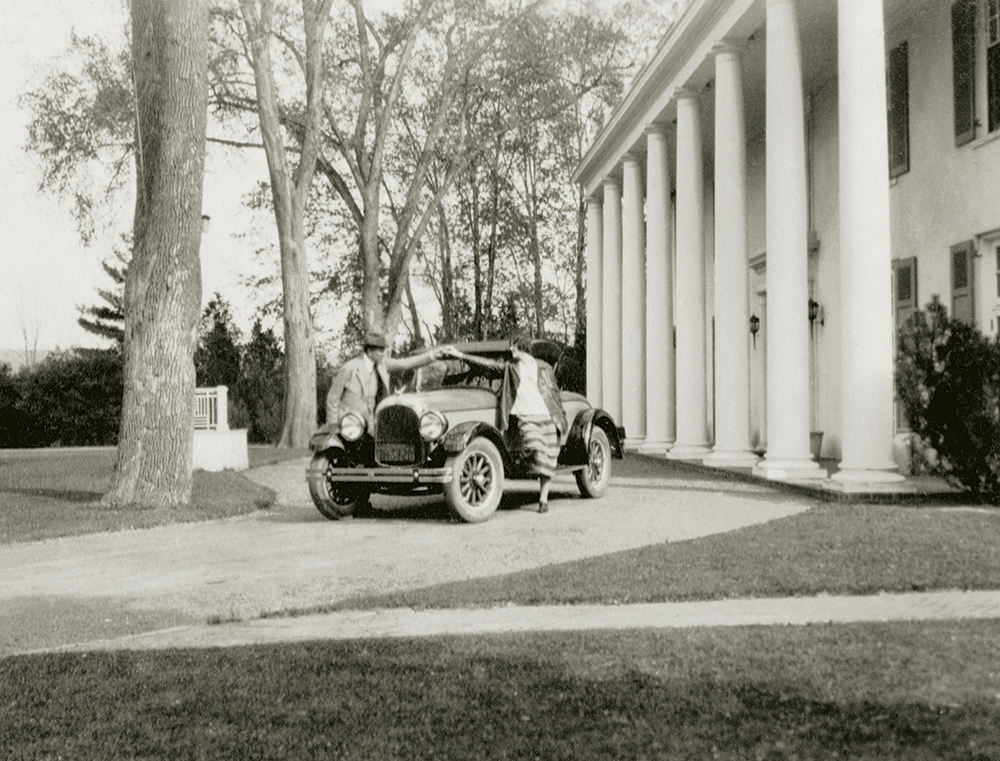 Tracy Dows ceremoniously presenting Margaret the keys to a 1926 Chrysler Imperial Roadster, the first year the car was introduced, for her nineteenth birthday in 1925.
