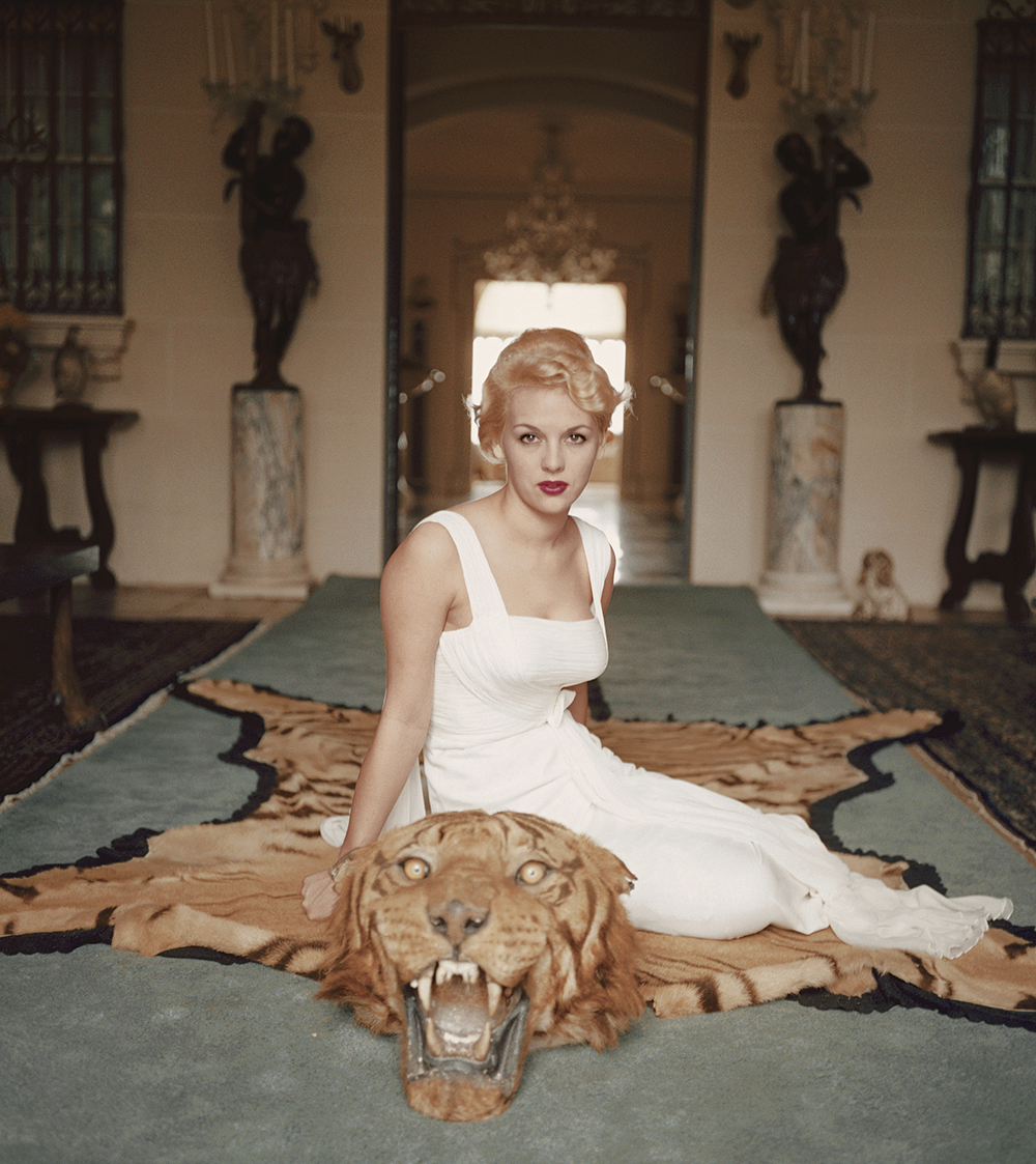 Lady Daphne Cameron sits on a tiger pelt in the trophy room of Laddie Sanford's Palm Beach house, 1959.     ©Slim Aarons/Getty Images.