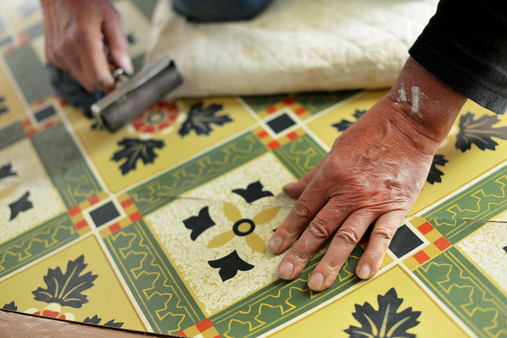 Hands of artist John Kraus installing his meticulously hand-painted floor cloth in the entryway.