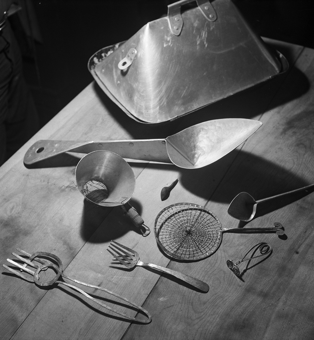 Forks, spoons, baby food pusher, milk skimmer, roasting pan and lid, and colander (c. 1935-48), Roxbury house kitchen, 1950.