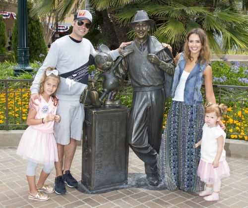 "(June 9, 2014) Actress Jessica Alba, her husband, Cash Warren, and daughters Haven, 3 (right), and Honor, celebrating her sixth birthday today, pose with a bronze statue of a young Walt Disney and his most famous creation, Mickey Mouse, called ""Storytellers"" at Disney California Adventure park in Anaheim, Calif., on Thursday. The statue reflects the optimistic outlook of Walt Disney upon his arrival in California in 1923 and is part of the Buena Vista Street area of the park. (Paul Hiffmeyer/Disneyland Resort)"