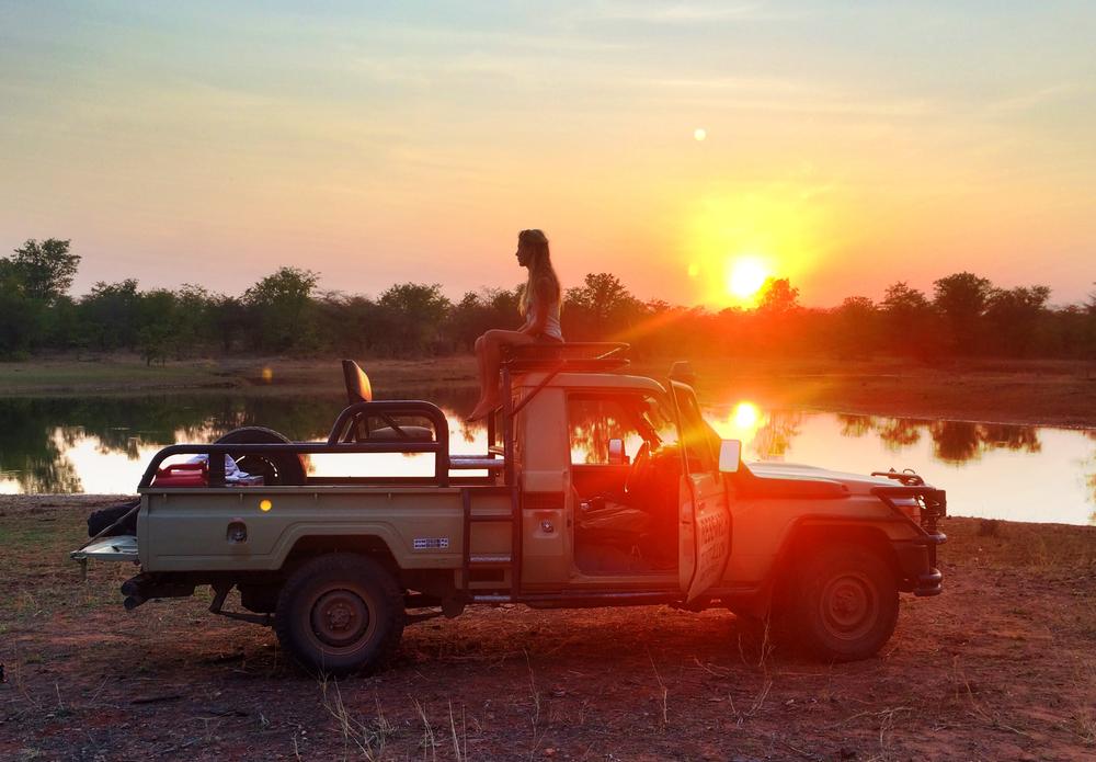 LAKE KARIBA MATUSADONA NATIONAL PARK ZIMBABWE AFRICA: Researcher Rae Kokes,  sitting on a research vehicle during sunset.  (Photo Credit: MATTHEW HOOD/ DON PERCIVAL/ Goddunnit Promotions)