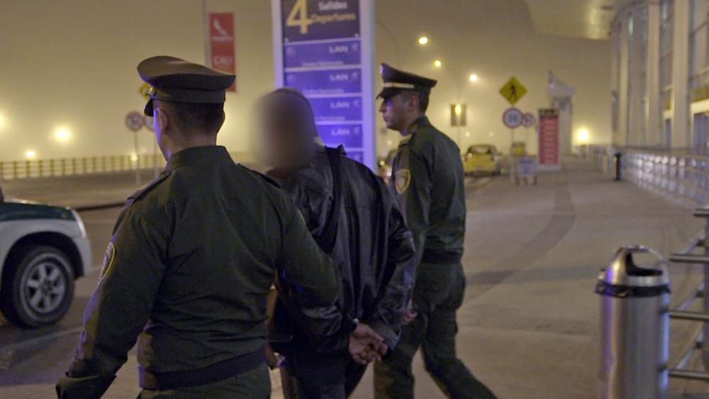 Los oficiales se llevan al detenido.jpg