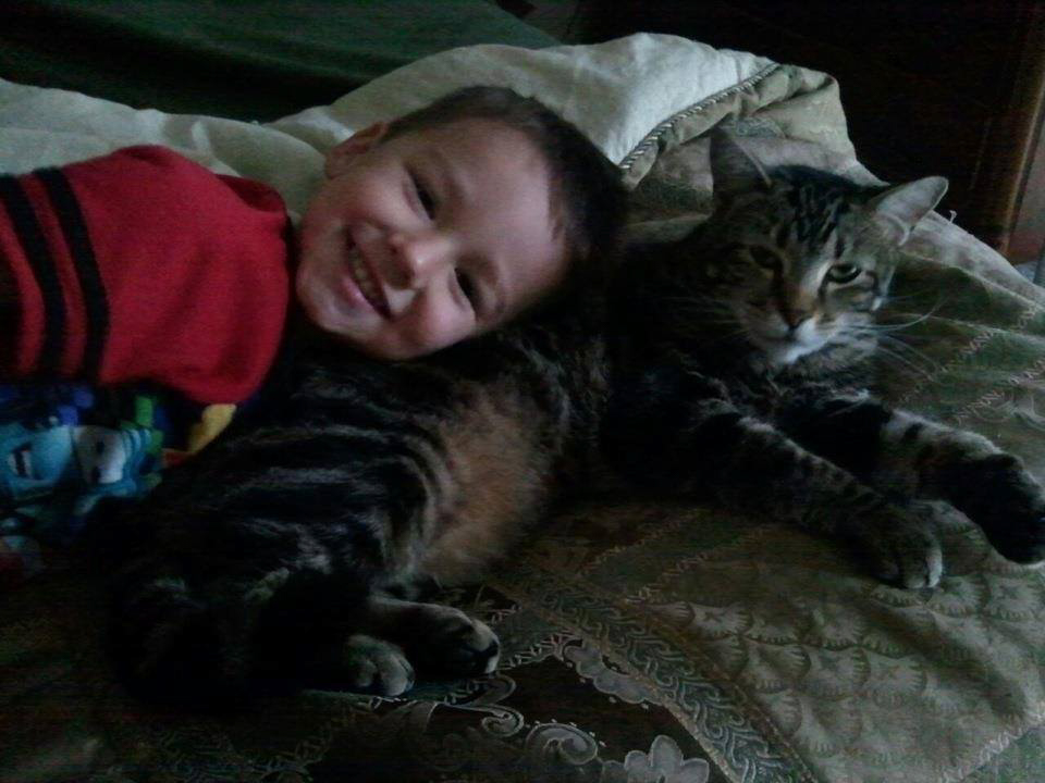 BAKERSFIELD, Calif. - Jeremy Triantafilo smiles and  lays down beside Tara the cat. These two grew up together, as brother and sister, so it makes sense that Tara, the protective older sister, was there for her little brother when he was in trouble. (National Geographic Channels/Roger Triantafilo)