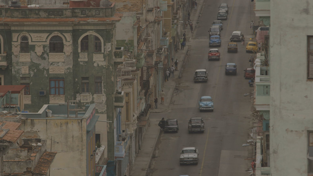 CUBA- This image contrasts a street full of cars and almendrones with the unique architecture of Cuba.