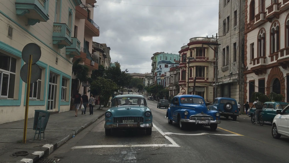 CUBA- This picture depicts two blue almendrones stopping at an intersection. The image also shows beautiful buildings that make up the background.