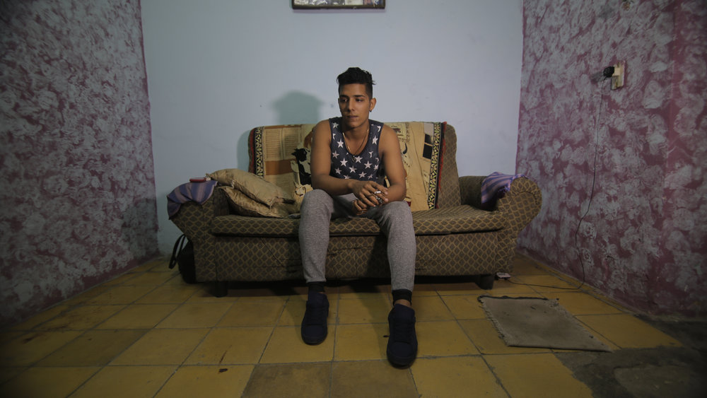 CUBA- Cuban painter, Hanoy Rodriguez, sat on a sofa in a room that he painted. He also wore a shirt with the American flag as a sign of hope during President Obama's visit to Cuba.