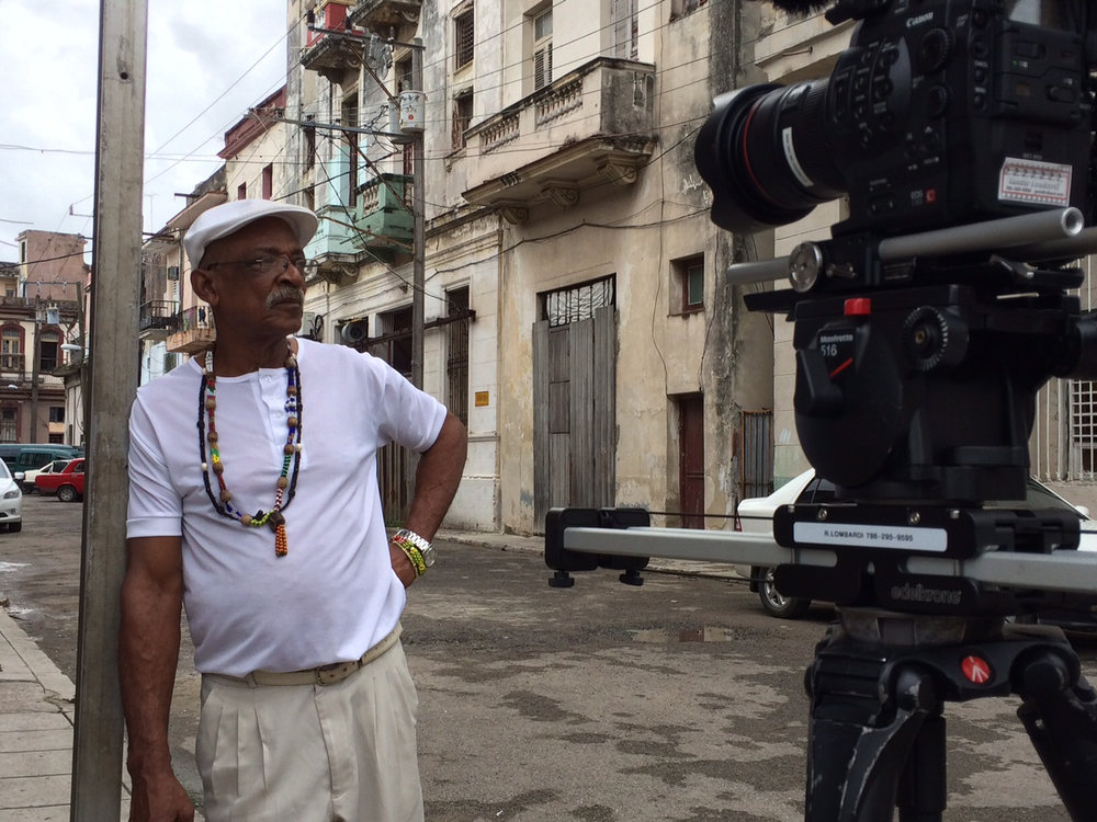 CUBA- The camera operator filmed b-roll of Julio Abreu Abreu, Babalawo, while he rested on a pole. We can admire the Cuban architecture in the background. 