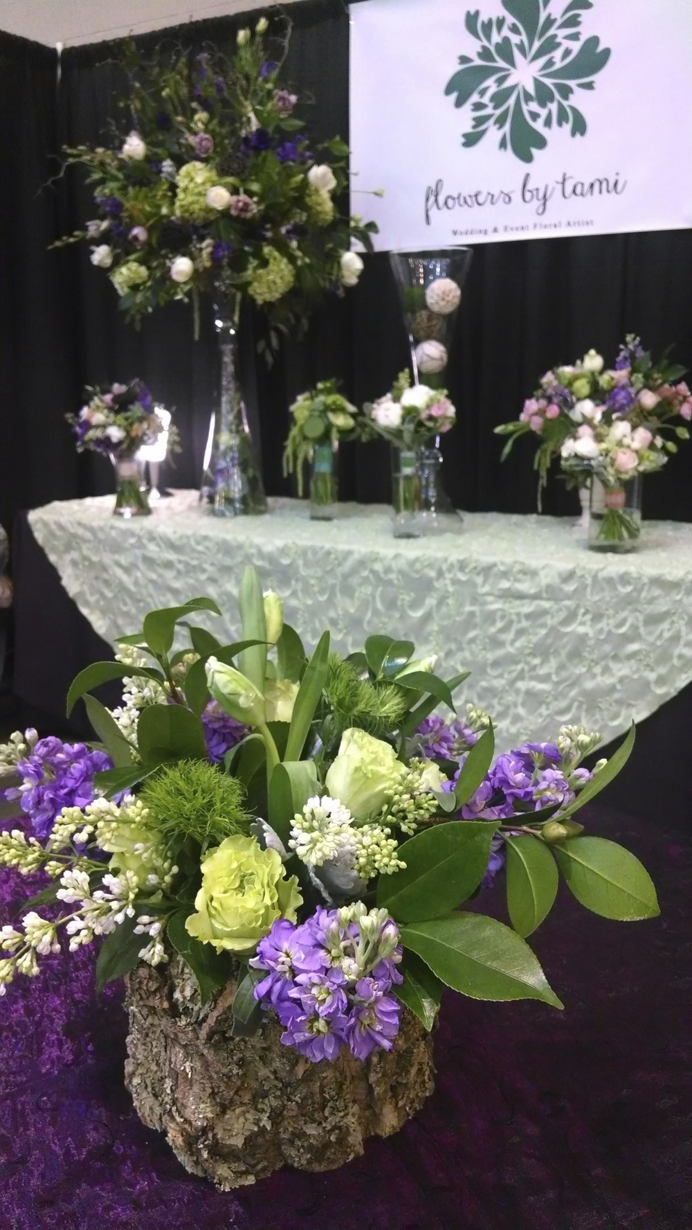 My booth. Centerpiece in corkwood container with green Roses, purple Stock, white Lilac, green Dianthus and Camellia foliage.
