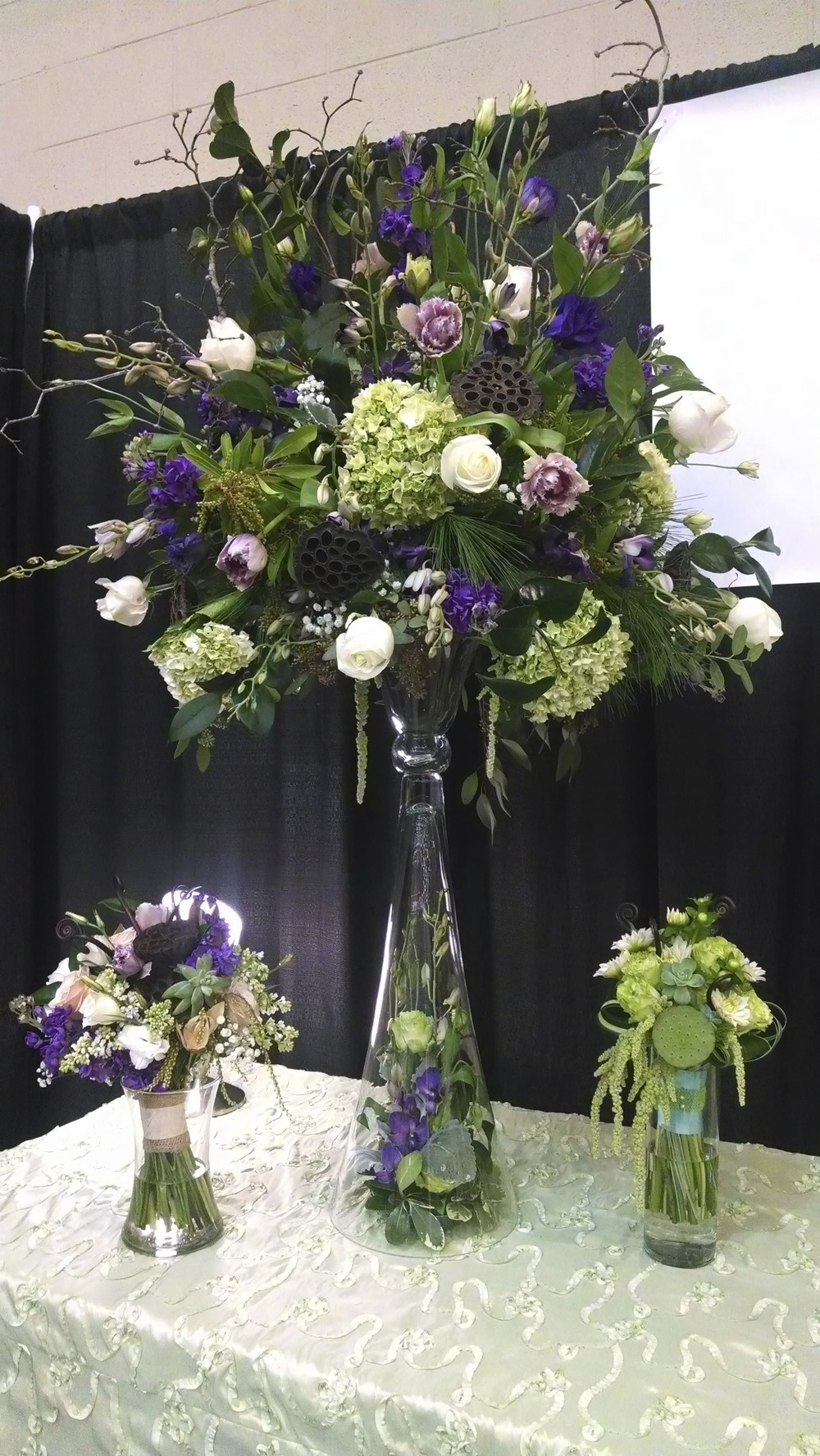 The main show piece in my booth.  A large scale arrangement, upraised on a reflection vase from accent decor.  Purple Stock, double fringed Tulips, Dendrobium Orchids, white Roses, green Hydrangeas, dried Lotus pods, Camellia foliage, Dogwood branches.