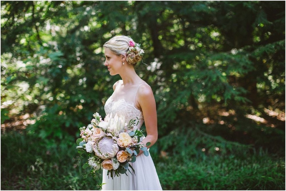 Beautiful Bride with Flowers in her Hair.  Her bouquet includes King Protea, Juliet Garden Roses, Lisianthus, Stock, Blushing Bride Protea, Jasmine vine and Eucalyptus.
