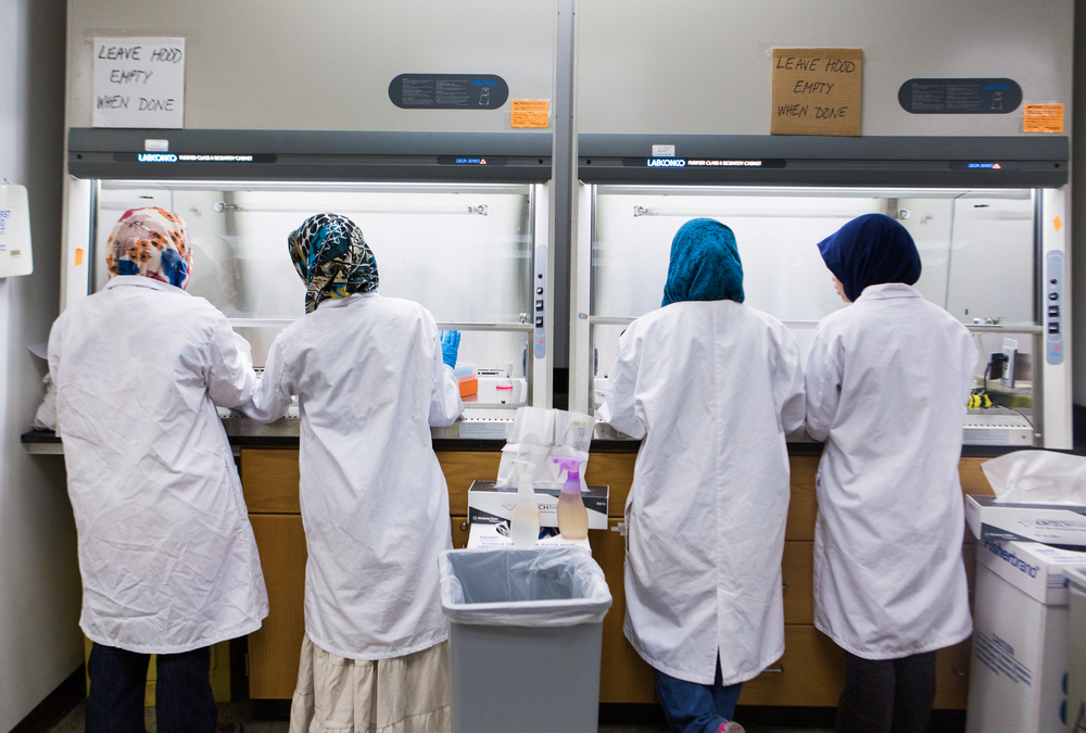 "Every year a small group of Malaysian women arrive at the Rochester Institute of Technology on government scholarships from their country to earn degrees in biotechnology. The women prepare for the lab in their ""Tissue Cultures"" class at the College of Science at Rochester Institute of Technology (RIT) on Dec 4, 2013.  Left to right : Aiman Rosdi, Norazleen Hashim, Kilala Rahman, and Fatini Busairi."