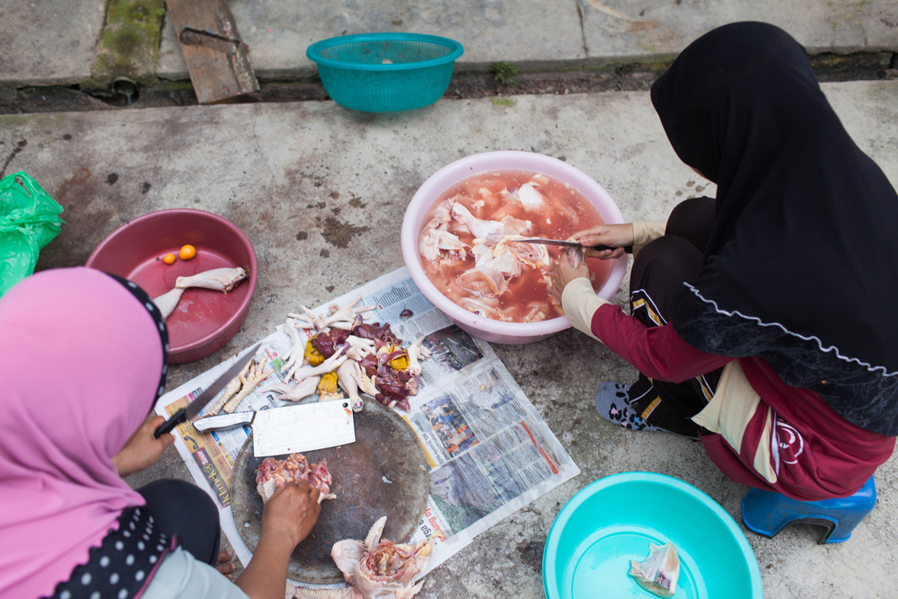 Fatini and her aunt cut the fat off a chicken in preperation to cook the Eid dinner, Jul 27, 2014.