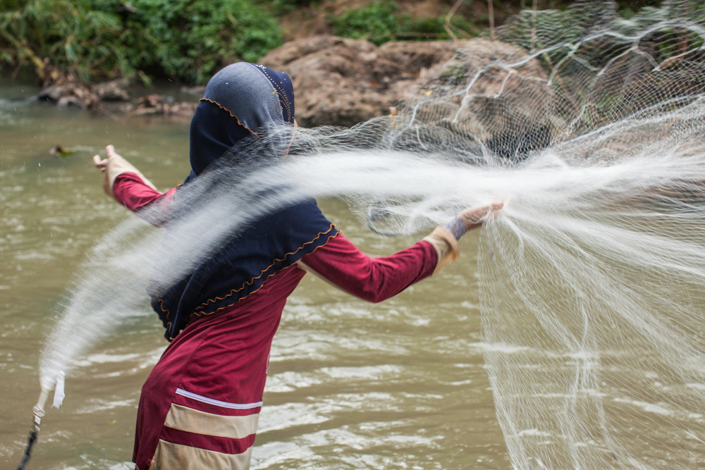 Casting a fishing net in a river on Jul 31, 2014.