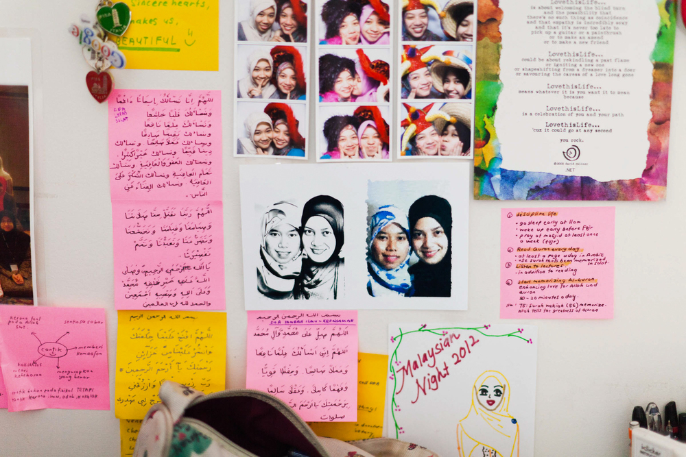 Aqlili Riana's bedroom wall filled with pictures of friends and religious reminders. May 9, 2012.