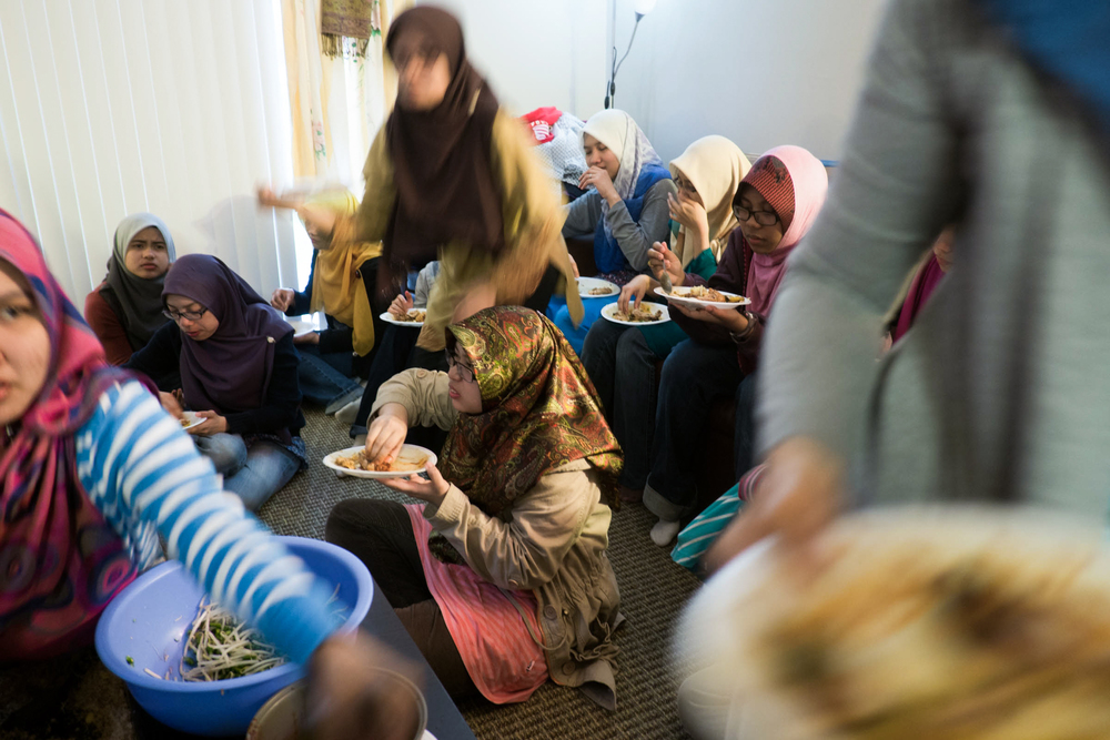 The women gather in an apartment to eat traditional food after a Malaysian Association meeting, Apr 19, 2013.