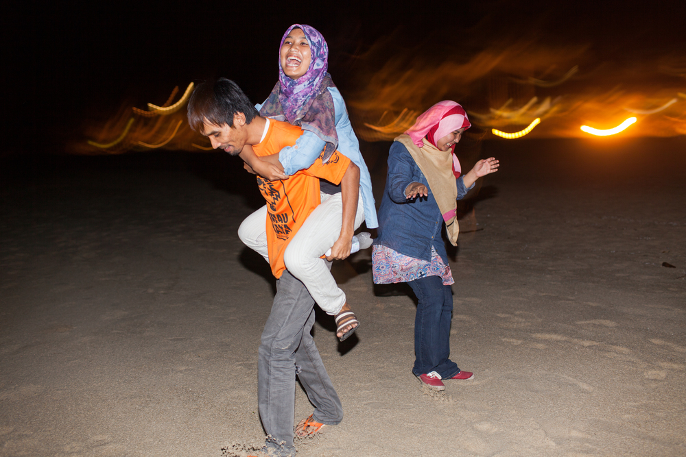 Nadia laughs as her youngest sister, Amieyra jumps on her brothers back at Teluk Chempedak Beach, Kuantan, Malaysia, July 23, 2014.