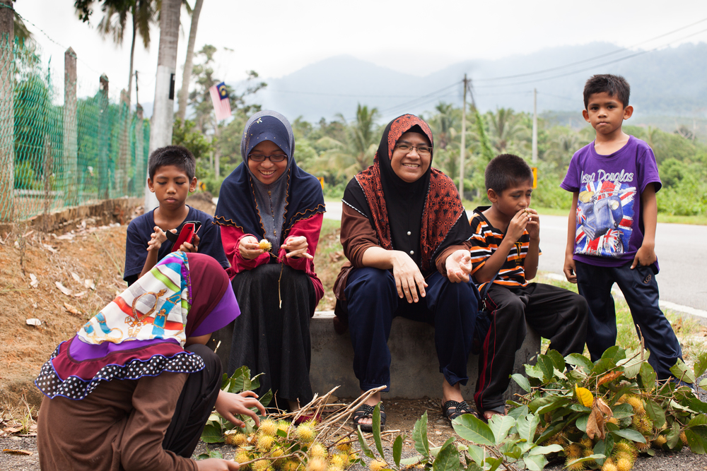 Fatini's sits and eats rambutan fruit with her aunt and cousins outside her grandmother's home, Kuala Pilah, Malaysia, July 22, 2014.
