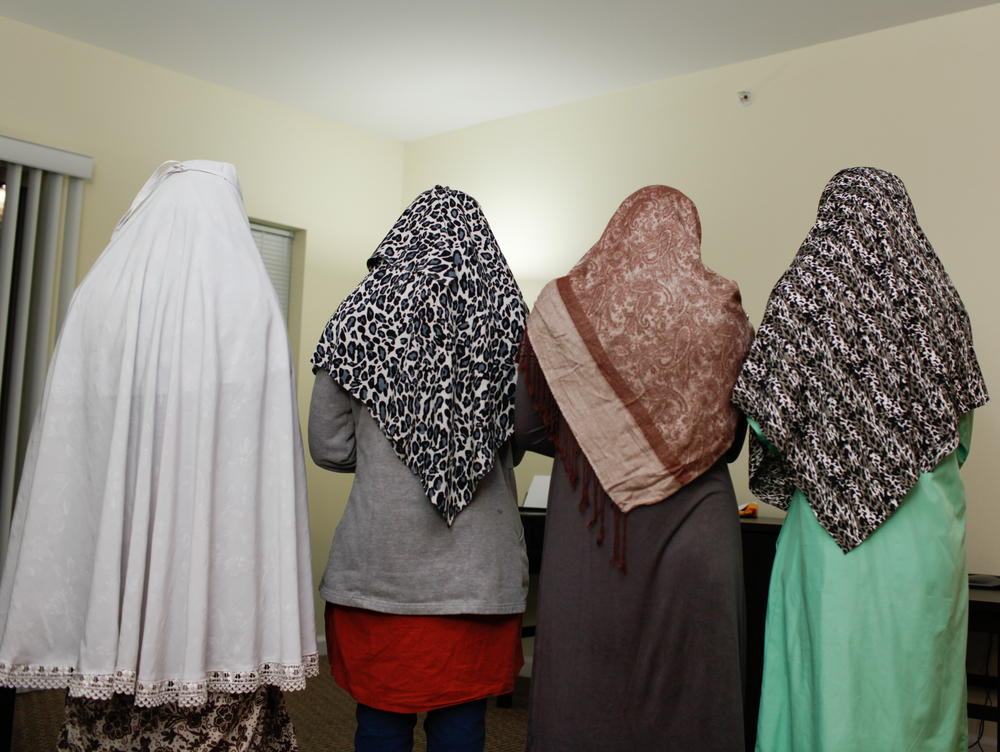 Before eating dinner, the women pray together in their apartment, Rochester N.Y., Oct 5, 2013.