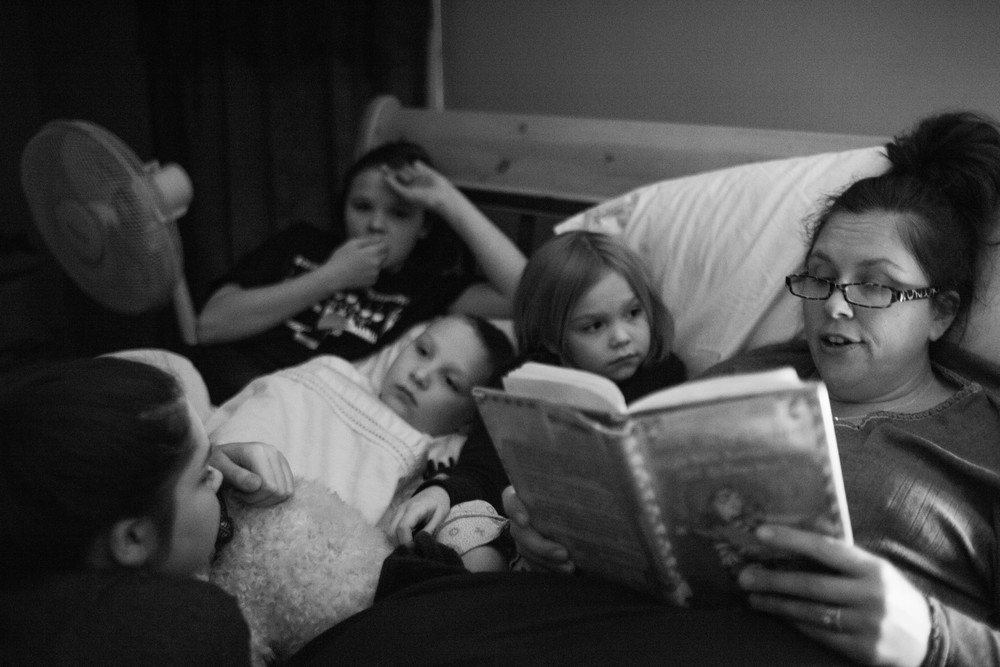 The four kids lay with Bridget in her bed while she reads them a story in her home in Baldwinsville, N.Y.  A bone marrow transplant is the only cure for Diamond Blackfan Aniema. All three sisters were tested and none proved to be a match.