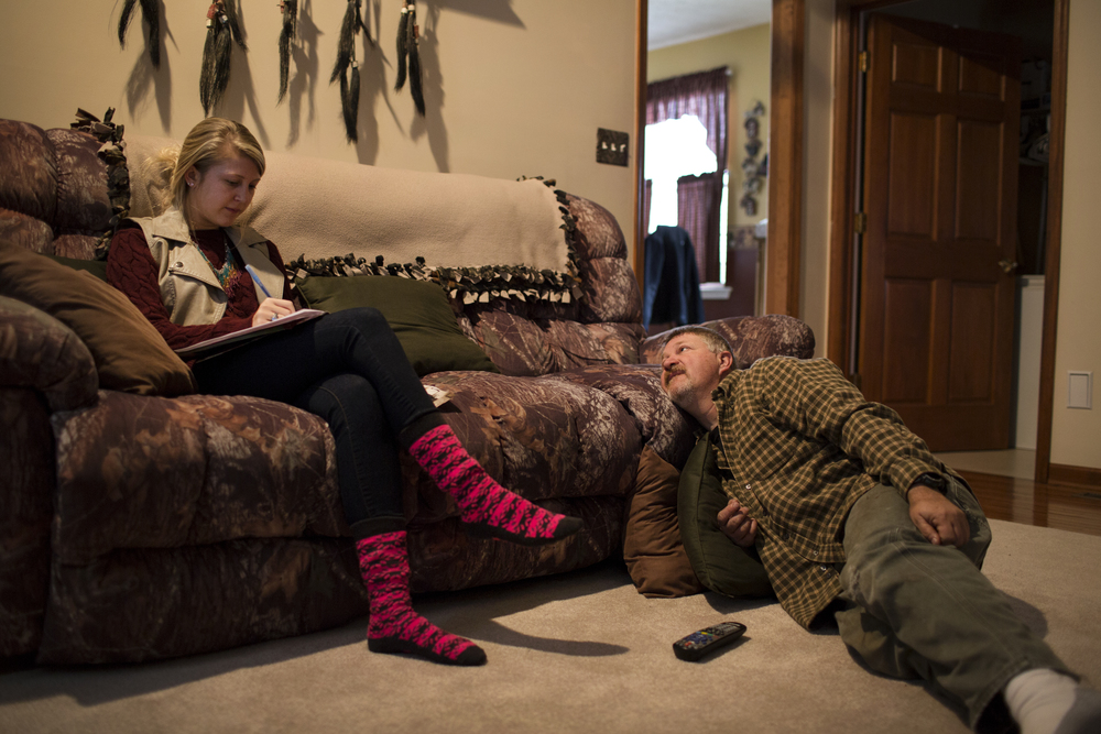 Tracy Groves lays in his living room while talking to Lindsay, his youngest daughter, at their home in Eldersburg, Maryland. Lindsay still lives at home and was studying for an upcoming EMT test.