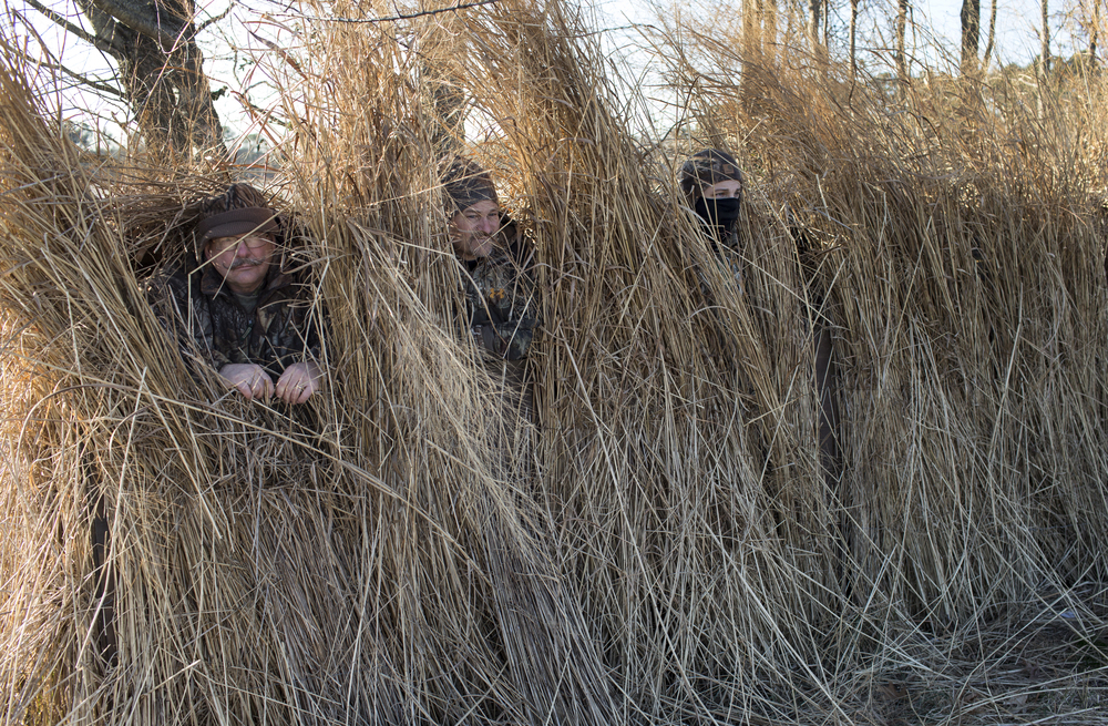 Troy Groves (C) stands with two other hunters in a blind on a goose hunt near Easton, Maryland.