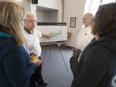 John Rennison, Hamilton Spectator    Rotary Club of Waterdown president Gary Flood, centre, explains the plan for a proposed skating rink for Waterdown Memorial Park to Chris Krawiec, left, Dave Banks, right, and Clare Mezgec, right, at an open-house Tuesday at Knox Presbyterian Church in Waterdown.