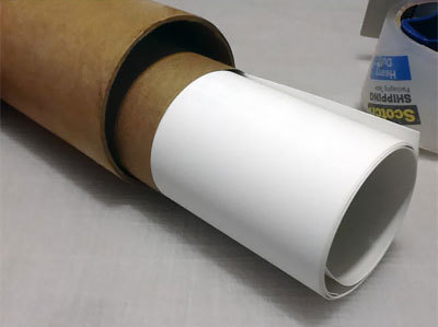Carefully rolled posters are covered with Kraft paper before placing in tubes for protection.