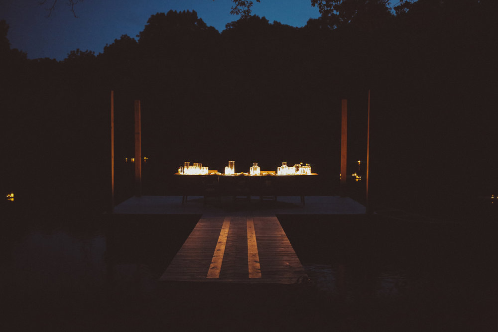 Dinner on a dock surrounded by floating, candle covered turkish rugs.