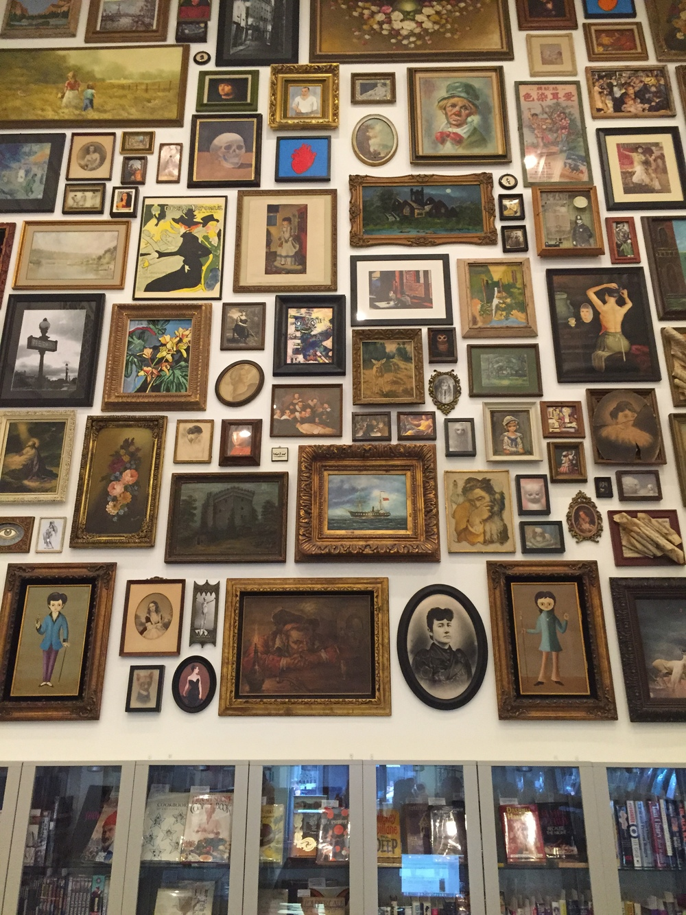 Vintage / thrift store art hung salon style on the back wall of The Last Bookstore Arts & Rare Books Annex.