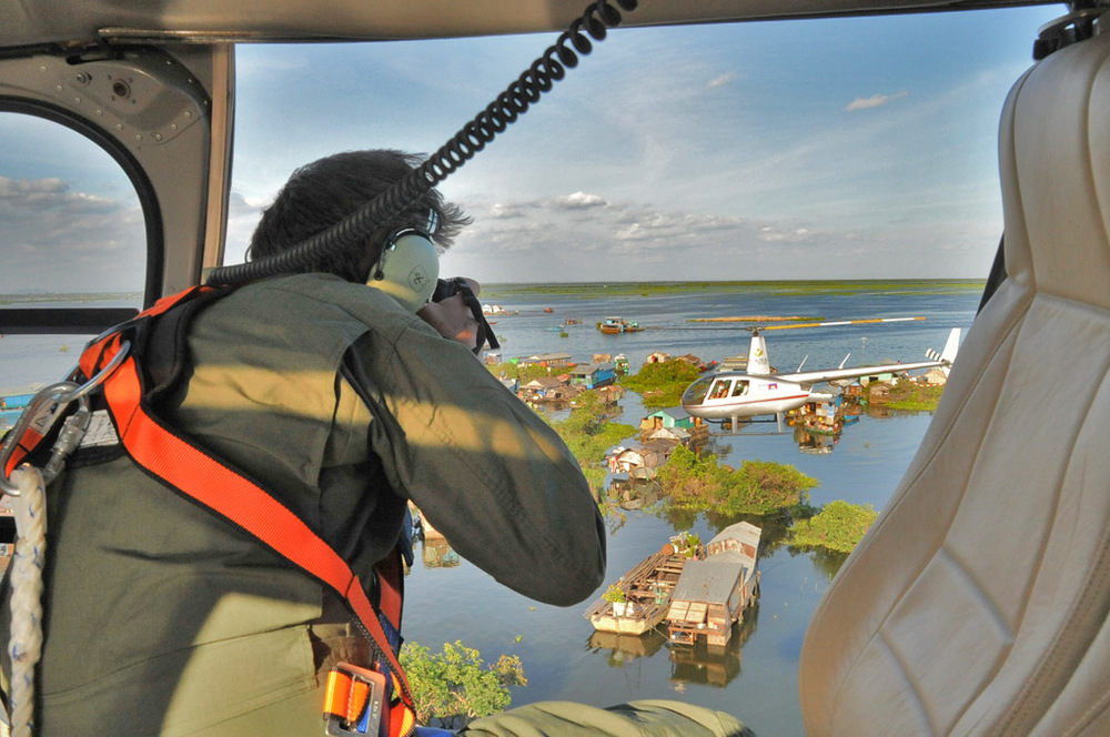 An R44 over the Tonle Sap Lake, Cambodia, taken by Alexis Bachofen in an AS350 helicopter