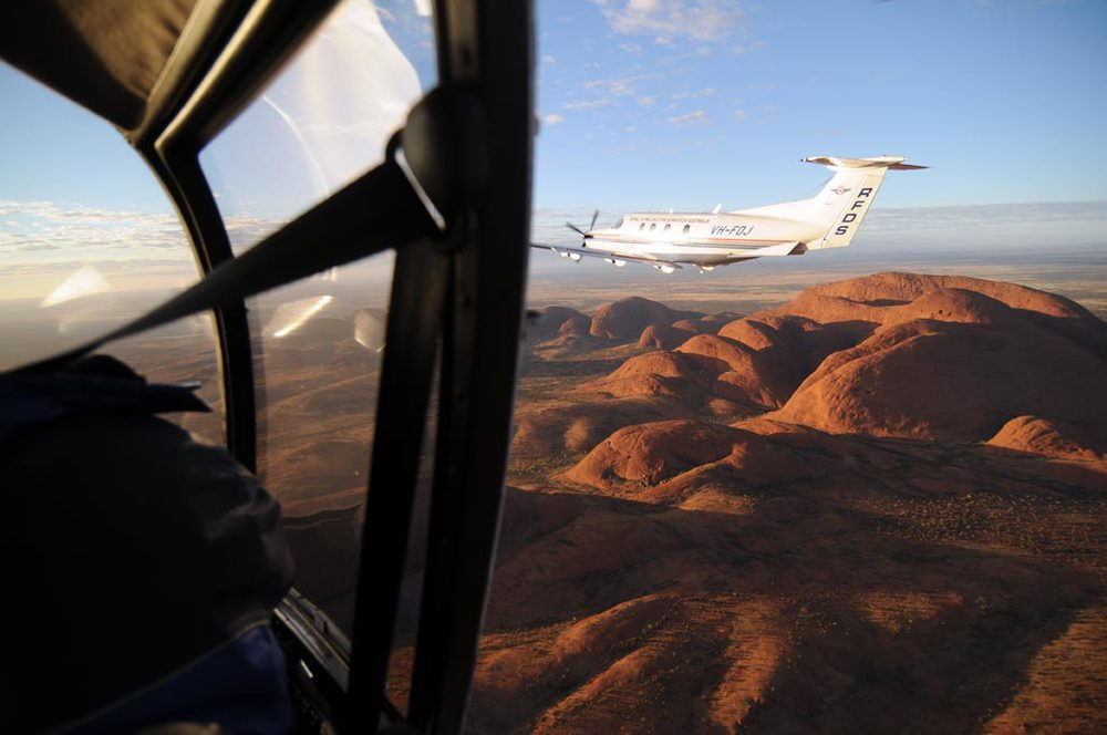 A Robinson R44, shooting an RFDS Pilatus PC12 over Kata Tjuta