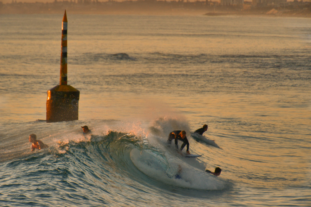 Catching a wave beside the old shark net pylon