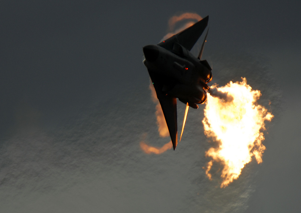 An RAAF F-111C turning with full afterburners, dumping fuel for a 'dump and burn' display