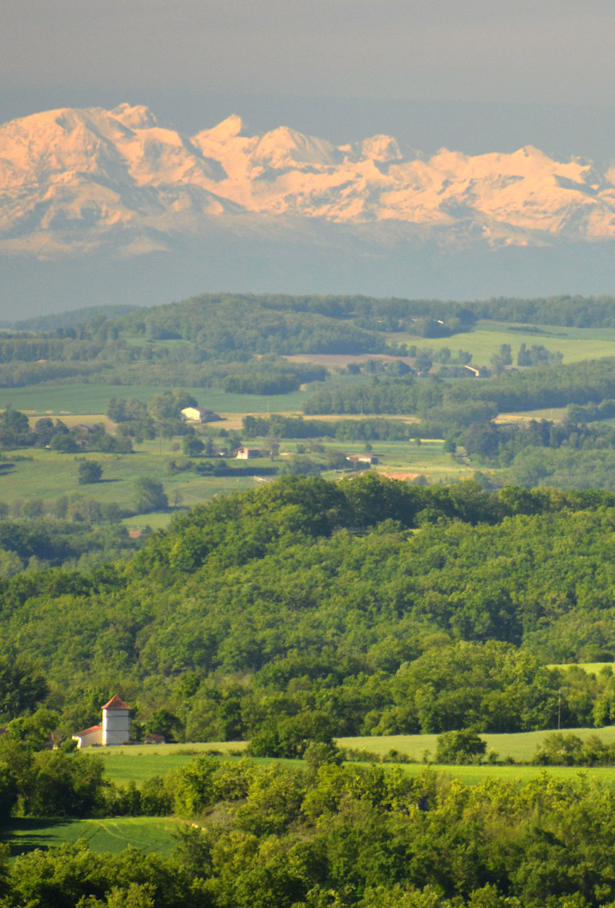 Long shot of a Pigeonnier with the Pyrenees as a backdrop