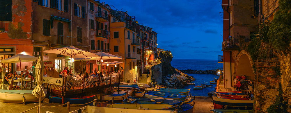 Dusk panorama of Riomaggiore, viewed from the harbour slipway